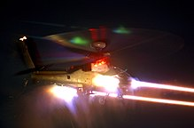 Photograph of an AgustaWestland Apache firing CRV7 rockets at night.