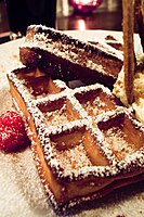 Thick, rectangular waffle deeply browned and topped with powdered sugar.