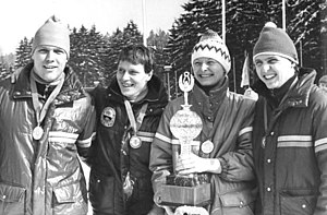 Four smiling people carrying medals around their neck are aligned shoulder-to-shoulder in an outdoor location with pine trees in the background. On the left, a man wears a shiny jacket and winter cap. Next to him, a second man with short dark hair wears a dark jacket with a badge. The third person is a woman wearing a jacket and an embroidered winter cap, and holds a trophy in her hands. The last person, on the right, is another man, also wearing a jacket and a winter cap.