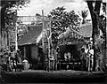 COLLECTIE TROPENMUSEUM Bewakers en verkopers bij een poort met wachthuis Soerabaja TMnr 60005130.jpg
