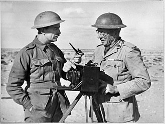 Frank Hurley - Hurley, on the right, discusses photographic opportunities for the forthcoming Battle of Bardia with an officer of the Australian 6th Division, Egypt, 1940