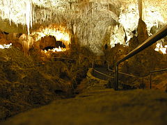 A picture of a partially illuminated cave with a jagged rock ceiling and a walkway extended into the cavern.