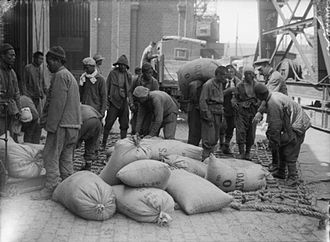 Chinese Labour Corps - Men of the Chinese Labour Corps load sacks of oats onto a lorry at Boulogne while supervised by a British officer (12 August 1917)