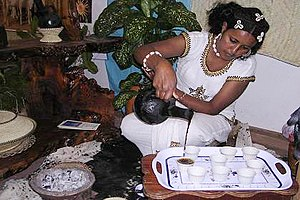 Culture of Eritrea - An Eritrean woman pouring traditionally brewed coffee into finjal from a jebena.