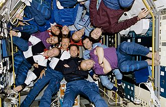 Ten people inside Spacelab Module in the Shuttle bay in June 1995, celebrating the docking of the Space Shuttle and Mir. Crewmembers of STS-71, Mir-18 and Mir-19 Pose for Inflight Picture - GPN-2002-000061 rotated.jpg