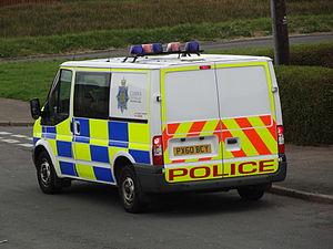Van - A Ford Transit van serving as a British police van. It has been modified mechanically and with reflective decals and red and blue  rooftop lights.