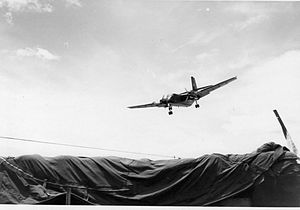 Large airplane descending over tarpaulin-covered area
