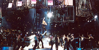 """Drowned World Tour - Madonna during the final performance of the show, """"Music"""", flanked by all her dancers."""