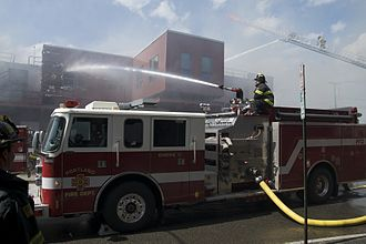 Deluge gun - A deck gun in the foreground puts water through a window while a ladder-mounted master stream in the background directs water through the collapsed roof.