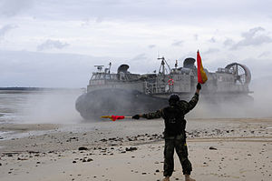 Defense.gov News Photo 110715-N-WV964-065 - A U.S. Navy sailor with Beachmaster Unit 1 directs a landing craft air cushion toward the beach during a water transport exercise with the.jpg
