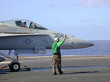 Side nose view of bluish gray jet aircraft on aircraft carrier out at sea on clear day. Green-topped personnel wearing earmuffs standing close by, preparing the aircraft for launch towards right