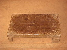 rectangular wooden stool with lines etched into the surface in four rows