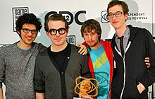 Four males from the development team stand with an atom-like trophy with a GDC backdrop. From left to right, Vreeland has long, messy hair, rectangular glasses, a TV static-like sweater, and is unshaven. His arm is around Fish, whose brown hair is combed back. He wears thick black glasses frames and a black shirt underneath a gray cardigan. McCartin has brownish-red hair and a goatee, and wears a Fez logo T-shirt underneath a red zippered hoodie. Bédard is a head taller than the bunch, and has short, brown hair, rectangular glasses, and is unshaven. He wears a black and white checkered dress shirt, a black tie, and a zippered, black hoodie.