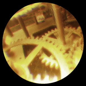 Fiberscope - A low quality fiberscope observing the inside of an antique clock mechanism. Note how individual fibers are discernable, as each fiber only relays one general color.