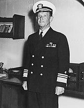 Portrait d'un homme en costume d'amiral dans un bureau.