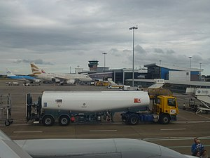 Airport apron - Apron at Leeds Bradford Airport showing narrowbody aircraft, service vehicles, a tanker and jet bridges.