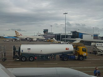 Airport apron - Apron at Leeds Bradford Airport showing narrowbody aircraft, service vehicles, a tanker, and jet bridges.