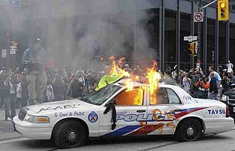 2010 G20 Toronto summit protests - A rioter on top of a Toronto Police Service cruiser in flames