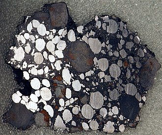 Carbonaceous chondrite - Gujba meteorite, a  bencubbinite found in Nigeria. Polished slice, 4.6 x 3.8 cm. Note the nickel-iron chondrules, which have been age-dated to 4.5627 billion years.