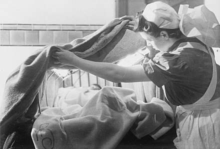 In London Hospital, England, 1941, nurse arranges an asbestos blanket over an electrically heated frame to create a hood over this patient to help warm them quickly Guy's Hospital- Life in a London Hospital, England, 1941 D2325.jpg