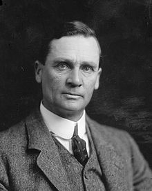 Shows a clean shaven man looking towards the camera. He wears a shirt and tie, a waistcoat, and a suit jacket.