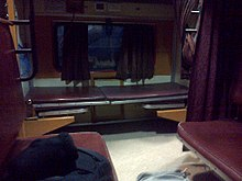 Train compartment with two seats and a bed