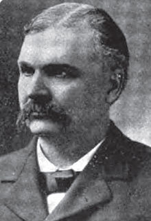 A man with graying hair and a dark mustache wearing a black jacket and tie and white shirt