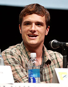 Man in a checked shirt sitting at a table, aside a microphone.