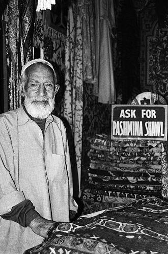 Pashmina - A Kashmiri man sells a pashmina shawl from Kashmir in a market in Delhi, India.