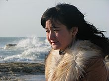 Young woman in a fur coat near the Caspian Sea