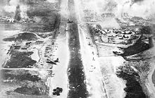 Black and white image from the rear of a plane showing a landing strip littered with damaged aircraft