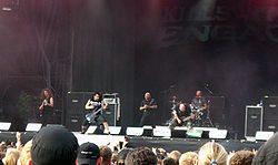Five men play instruments onstage; one sings, one plays a drum set, one plays bass guitar, and two play electric guitar. An audience watches the band play.