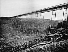 A black-and-white photo of a bridge crossing a valley