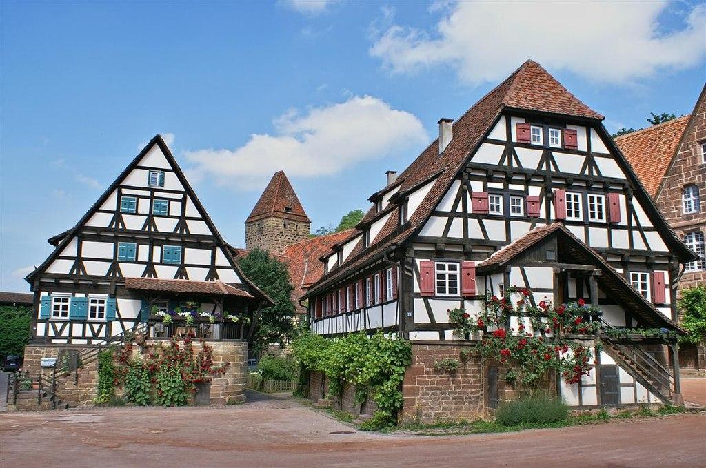 Kloster Maulbronn: Vordergrund: zwei Fachwerkhäuser (Haberkasten, Pfisterei), im Hintergrund: Hexenturm
