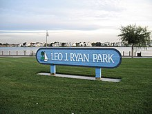 "A blue sign stands in the middle of a park. ""Leo J. Ryan Park"" is written on it."