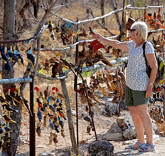 Tourist buying handicrafts in Namibia, an important source of income for some tourist destinations Local handicraft, Etosha National Park (Namibia).jpg