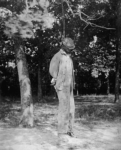 An African-American man lynched from a tree. His face is partially concealed by the angle of the photograph and his hat.