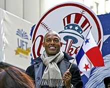 "Mariano Rivera wearing a dark pea coat and gray scarf smiles while holding a red, white, and blue flag. He stands in front of a red, white, and blue logo that reads ""Yankees""."