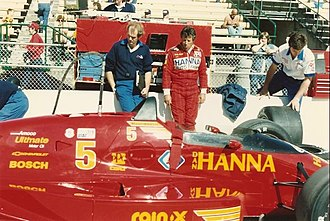 1987 Indianapolis 500 - Pole-sitter Mario Andretti waits by his car during a practice session.
