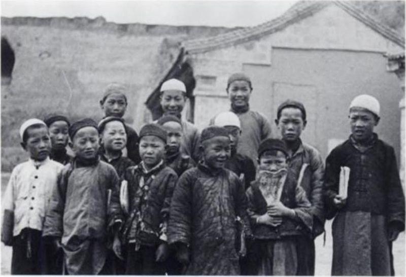 Muslim schoolboys with books and bone slates.jpg
