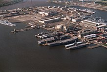An overhead view of a large shipyard. Various ships can be seen tied up, with several structures visible within the yard.