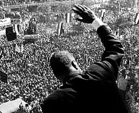 The back of a man waving to the throng below