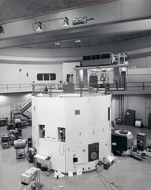 The black-and-white photograph is of a large room that contains a lot of electronic equipment. The lower half of the image contains a cylindrical white container that is a nuclear reactor. There is a walkway at the top of the reactor, which leads back to a control room where two men are sitting.