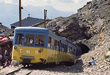mountain railway train emerging from a tunnel