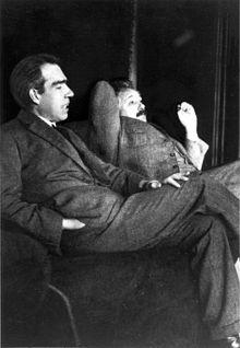 Hai nhà khoa học đang ngồi thư giãn. Bohr với mái tóc đen đang nói chuyện với Einstein.
