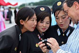 Tourism in North Korea - A tourist taking photos with locals