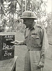 "Three-quarter-length outdoor portrait of moustacioed man in light tropical military uniform with pith helmet and pilot's wings on left breast pocket, placing folded paper into a box marked ""RAAF BALLOT BOX"""