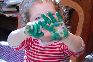 English: Little girl shows her hands covered i...
