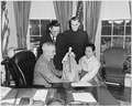 Photograph of President Truman in the Oval Office, receiving a doll from Dr. Helen Kim, a Korean educator, as Dr.... - NARA - 200314.tif