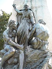 A bronze monument featuring a Christian missionary holding a cross high over the heads of two North American aboriginal peoples sitting at his feet